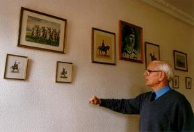A picture of a man pointing to some pictures on a wall