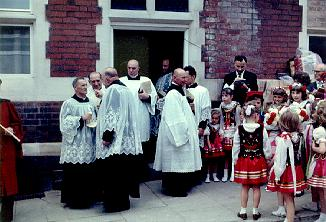 A picture of the priests gathering outside the church after the ceremony with polish girls in national costumes, 1957.
