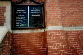 A picture of a wall with a board showing times of church services