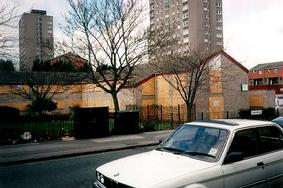 A picture of boarded up houses with highrise flats in the distance