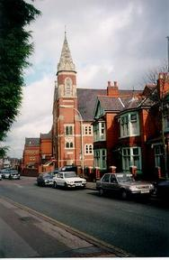 A picture of a large church on the side of a road with terraced houses on either side