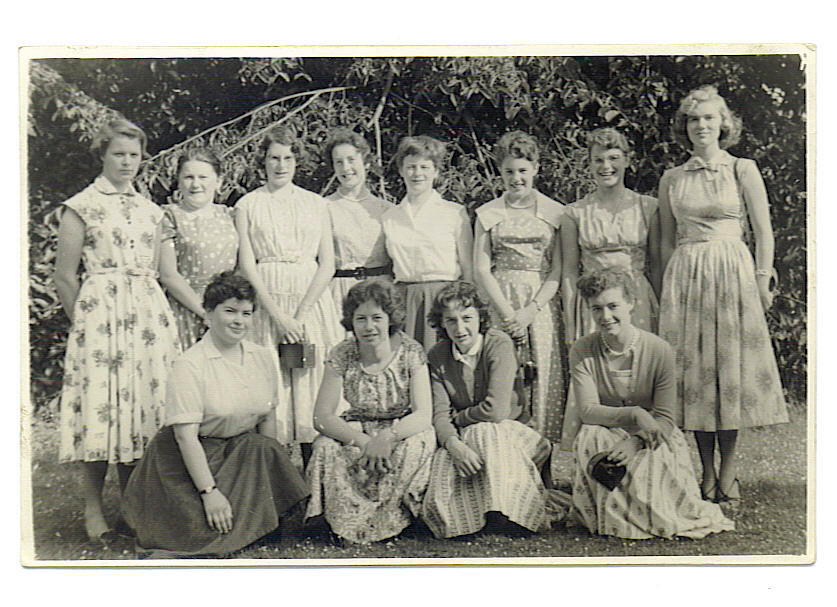 12 young women posing for a group picture in a garden.