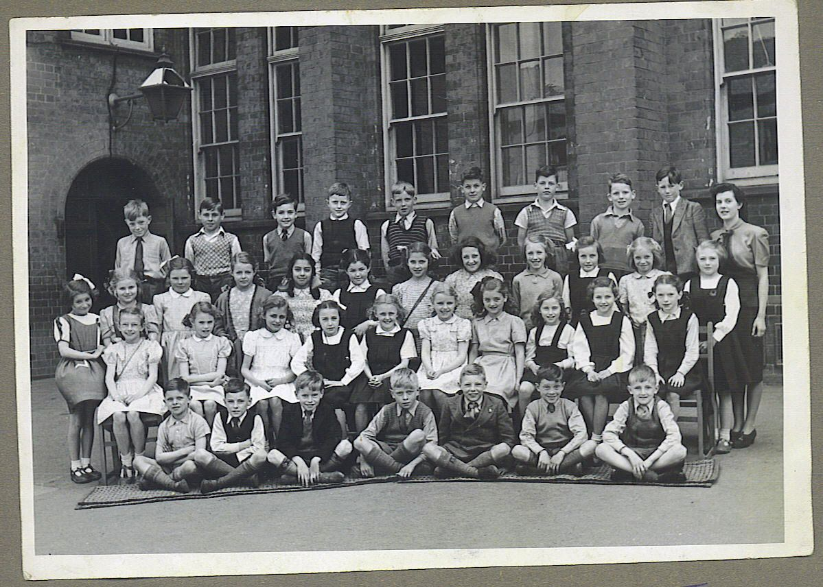 A large group of boys and girls posed for a group shot in front of a school building with a teacher.