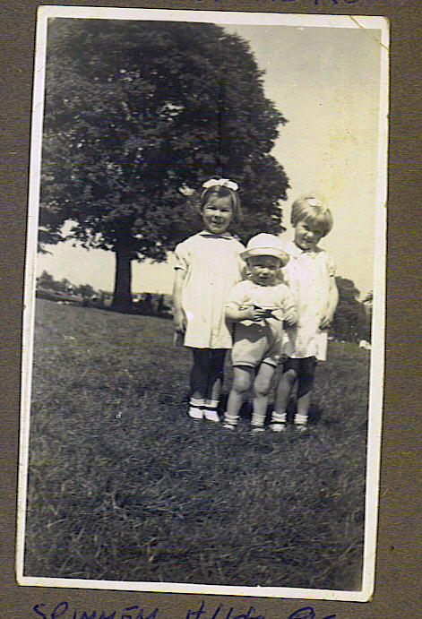Three young children standing in a publivc park.