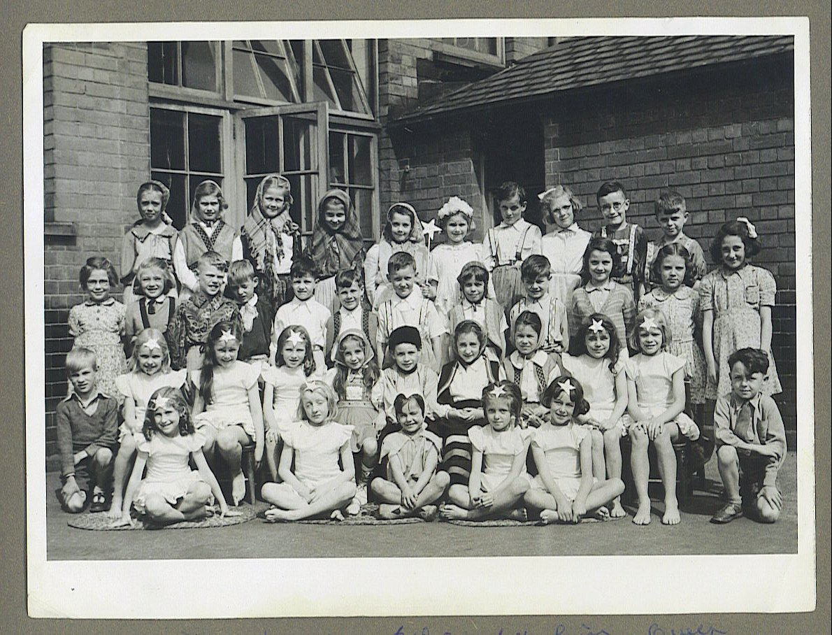 A large group of boys and girls dressed in costume as elves and fairies in front of a school building.