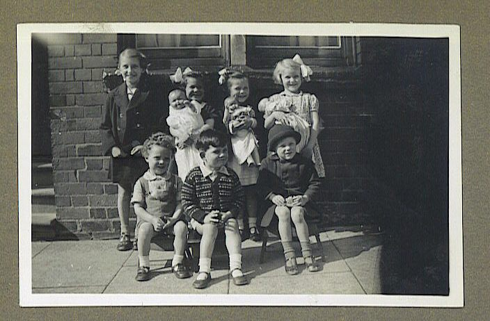 Seven children posing for a group shot on the street in front of a terraced house.