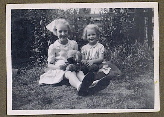 Two young girls sitting on the grass in a garden.