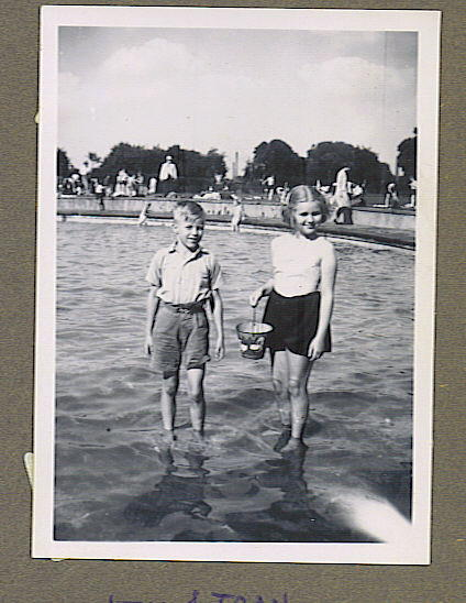 A boy and girl standing in an open air paddling pool.