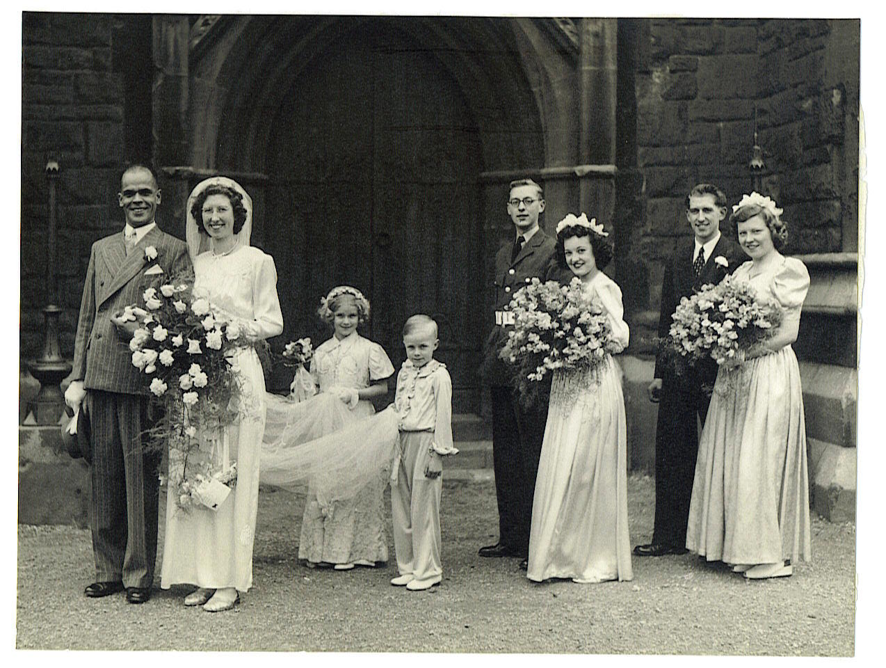 A bride and groom and their bridesmaids outside a church.