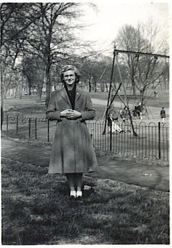 A young woman standing facing the camera in a public park.