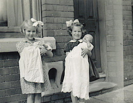 Two young girls crading a doll each in a terraced street outside a front door.