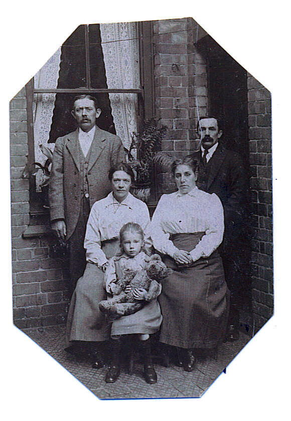 An edwardian family group posing for the camera in the backyard of a terraced house.