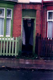 A picture of a house with the door open showing washing drying in the hallway