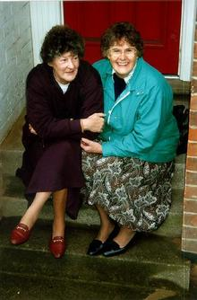 A picture of two women sat on the front steps of a house