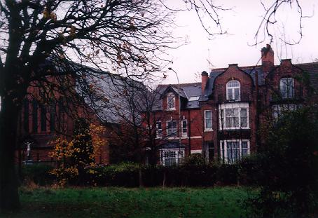 A picture of a tall terraced house from a park