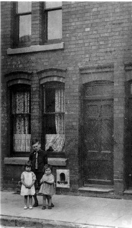 A picture of the outside our terraced house,1938, we stood to have our photos taken. Brother Norman had measels and is looking through the window.