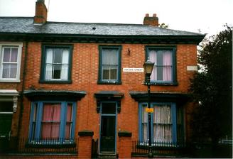 A picture of a double fronted terraced house with an old lamppost in front of it