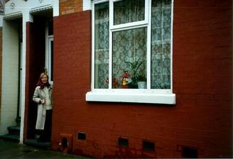 A picture of a row of terraced houses with a woman leaning out of the doorway of one