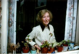 A picture of a woman in front window and some plants