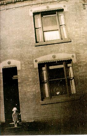 A photograph of a young child standing in the doorway of a terraced house