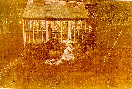 A picture of a young child in front of a greenhouse