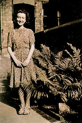 An old picture of a woman standing in a back garden next to a large fern