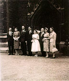 A picture of a wedding group outside of a church