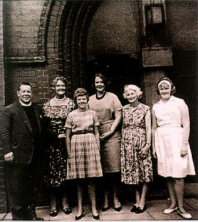 A picture of a group standing outside a church.