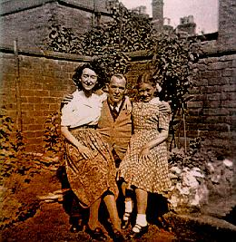 A picture of a man with two girls sitting on his knee
