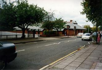 A picture of a road with a pelican crossing.  On the far side of the road is a new low brick building