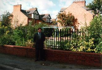 A picture of a man in a suit standing in front of a low wall with railings behind