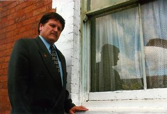 A picture of a man in front of a window