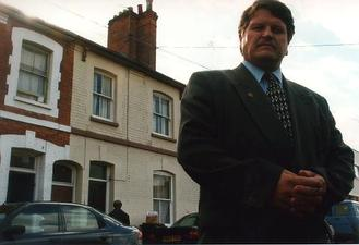 A picture of a man in a suit standing in front of a row of terraced houses
