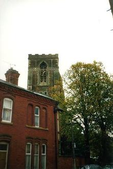A picture of a row of terraced houses with a church behind