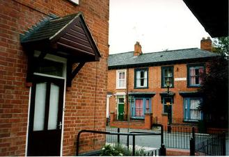 A picture of the corner of a house with terraced houses in the background