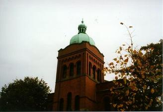 A picture of a brick tower with a green domed top