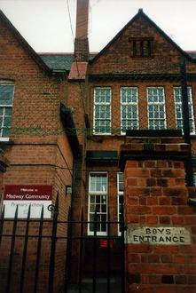A picture of a large brick building with the sign 'BOYS ENTRANCE' on the wall.