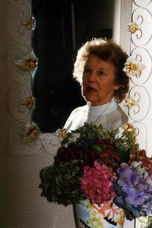 A picture of a relection in a mirror showing the head and shoulders of a woman.  In front of the mirror is a vase of flowers