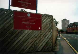 A picture of a road bounded on one side by a wooden fence