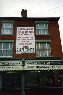 A picture of a newsagents with a large sign above it