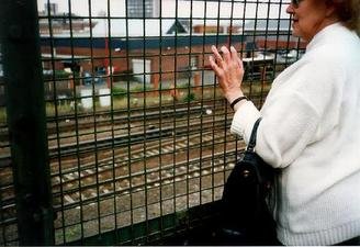 A picture of a woman looking through a wire fence at the train lines below.