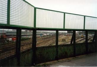 A picture of a path with high wire fencing on the side nearest to the railway lines