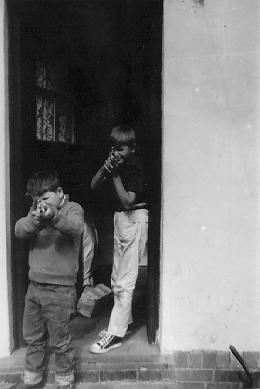 A photograph of two young boys in the doorway of a house pointing toy guns at the photographer