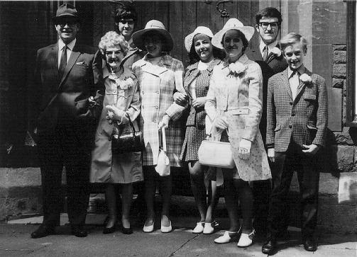 A photograph of a wedding group standing outside a church