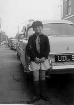 A picture of a boy in a cubscout uniform standing in front of a car