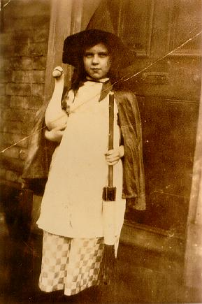 A picture of a young girl holding a broom and toy goose