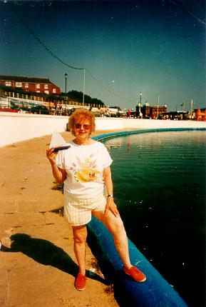 A picture of a woman standing next to a boating pool